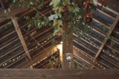 Autumn wedding turning leaves barn beams fairy lights ladders foliage hanging candles lanterns event design styling woodland verdigris