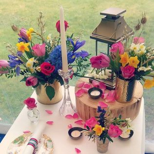 Colourful rusic and gold table centre idea with loose rose petals and vintage china, wood round and tea light holders